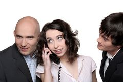 Businessmen Phone. A young businesswoman holding a telephone receiver surrounded by two businessmen listening Stock Photography