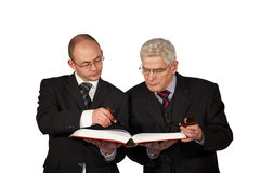 Businessmen with pipes reading a book Stock Images