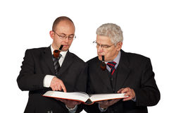 Businessmen with pipes reading a book Royalty Free Stock Image