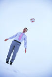 Businessmen playing soccer in winter field Stock Photo