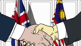 Businessmen or politicians shake hands against flags of Britain and Malaysia. Official meeting or cooperation related. Businessmen shake hands against flags of royalty free illustration