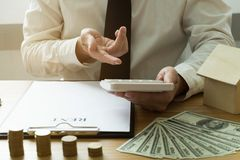 Businessmen present price contract on trading - rent a house to stock image