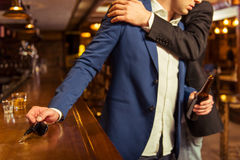Businessmen in pub. Young drunk businessman is holding a bottle of beer and reaching car keys on bar counter in pub, another men is stopping him Royalty Free Stock Photos