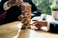 Businessmen pulling block wooden fail danger. Tower challenge game building consturction protect plan and project teamwork for control risk shape Stock Images