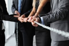 Businessmen pulling chain Stock Photo