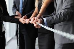 Businessmen pulling chain Stock Photo