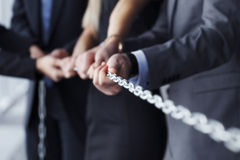 Businessmen pulling chain Royalty Free Stock Photos