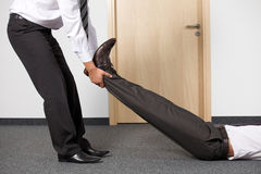 Businessmen pulling colleague's leg at office Stock Photos