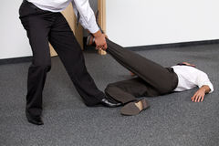 Businessmen pulling colleague's leg at office Royalty Free Stock Photography