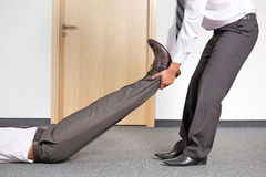 Businessmen pulling colleague's leg at office Royalty Free Stock Images