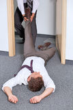 Businessmen pulling colleague's leg at office Royalty Free Stock Photos