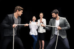 Businessmen pulling over rope with businesswomen near by royalty free stock photo
