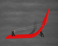 Businessmen pulling up growing red arrow Stock Images