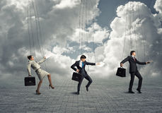 Businessmen puppets. Business people puppets hanging by a thread royalty free stock images