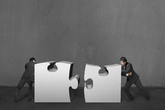 Businessmen push two heavy puzzles together in concrete wall bac Royalty Free Stock Images