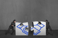 Businessmen push two heavy puzzles together with shake hand draw. Ing in concrete wall background Royalty Free Stock Photography