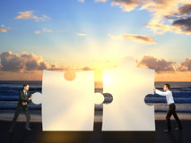 Businessmen pushing puzzle pieces together. Two businessmen pushing puzzle pieces together on sea background with setting sun. Cooperation concept Stock Photos