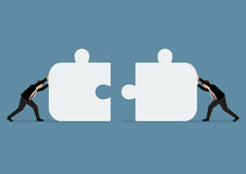 Businessmen pushing two jigsaw pieces together Royalty Free Stock Photo