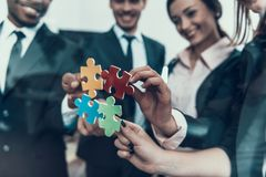 Businessmen put together parts of common puzzle together. Successful negotiations concept. Folding of puzzle. Finding approach to person stock images