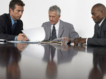 Businessmen Reading Documents In Conference Room Royalty Free Stock Photography