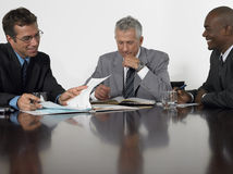 Businessmen Reading Documents In Conference Room Royalty Free Stock Images