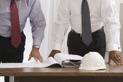 Businessmen reviewing blueprints royalty free stock photo