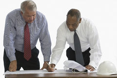 Businessmen reviewing blueprints Royalty Free Stock Images