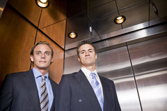Businessmen riding in elevator Royalty Free Stock Image