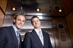 Businessmen riding in elevator Stock Photography