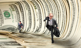 Businessmen running in dollar tunnel Stock Photo