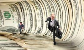 Businessmen running in dollar tunnel Stock Photo