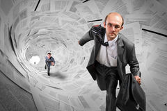 Businessmen running inside documents tunnel Royalty Free Stock Images