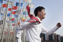 Businessmen running and smiling with flagpoles in background. Royalty Free Stock Photography