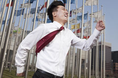 Businessmen running and smiling with flagpoles in background. Royalty Free Stock Photos