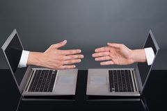 Businessmen's hands emitting from laptops representing deal Lizenzfreie Stockbilder