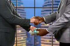 Businessmen's handshake and money transfer. Royalty Free Stock Images