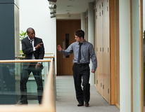 Businessmen saying goodbye in a corridor Royalty Free Stock Photography