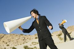 Businessmen Screaming Through Megaphones In Desert. Two businessmen screaming through megaphones in the desert Royalty Free Stock Photography