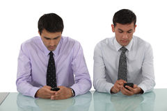 Businessmen sending text messages Royalty Free Stock Image