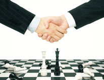 Businessmen shake hands above chess board Stock Images
