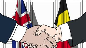 Businessmen or politicians shake hands against flags of Britain and Belgium. Official meeting or cooperation related. Businessmen shake hands against flags of stock illustration
