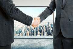 Businessmen shake hands at city background Royalty Free Stock Photography