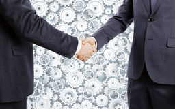 Businessmen shake hands at cogwheels background Royalty Free Stock Image