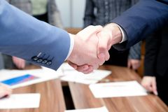 Businessmen shake hands each other stock images