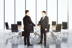 Businessmen shake hands in empty conference room Stock Images
