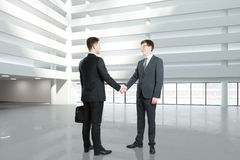 Businessmen shake hands in empty hall of business center royalty free stock images