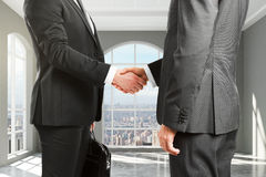Businessmen shake hands in empty loft room with city view Royalty Free Stock Photography