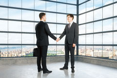 Businessmen shake hands in empty loft room Stock Photography