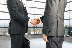 Businessmen shake hands in empty loft style room with glassy win Stock Photography