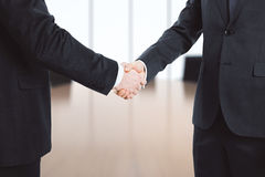 Businessmen shake hands in empty office Royalty Free Stock Photo